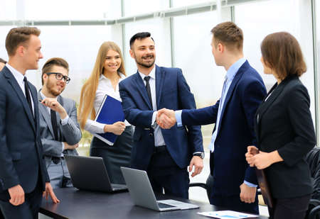 Group of confident business people in formalwear sitting at the table together and smiling while two men handshaking