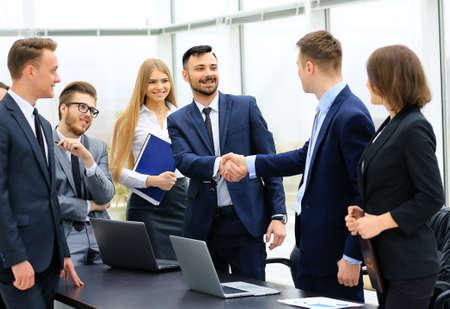 Gruppe überzeugte Geschäftsleute, die in Abendkleidung am Tisch zusammen sitzen und lächelnd, während zwei Männer Händeschütteln