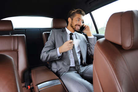 Attractive businessman talking on the phone in a car Stock Photo