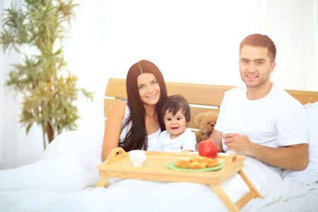bed and breakfast: Smiling family having breakfast sitting on bed at home Stock Photo