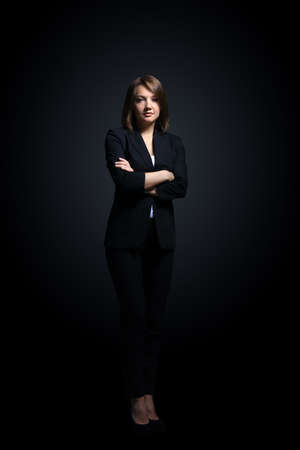 folding arms: Happy businesswoman wearing black suit standing and folding arms