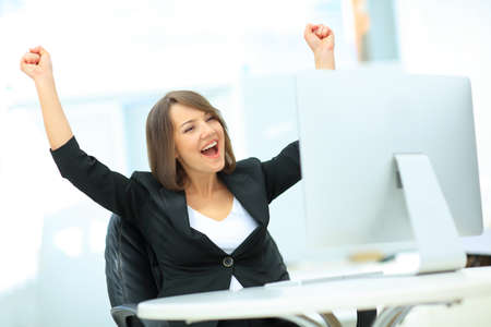 woman in office: Portrait of happy young successful businesswoman celebrate something with arms up
