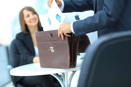 getting out: Businessman holding and getting out documents with graphs from his leather briefcase. Stock Photo