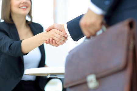 An attractive woman and man business team shaking hands at office
