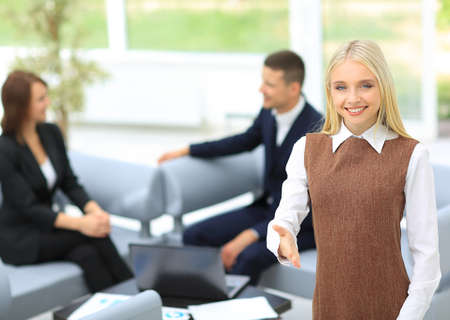 modern businesswoman: Beautiful modern businesswoman invites to cooperation with colleague on background