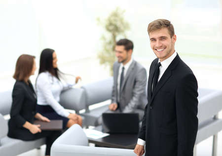 finance director: Successful business man standing with his staff in background at office Stock Photo