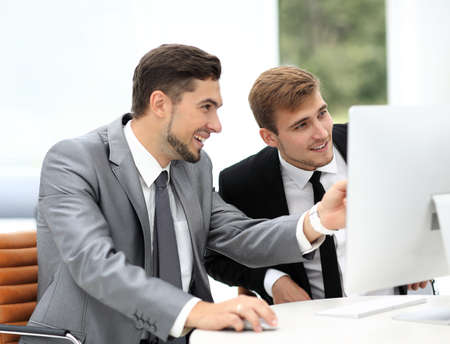 personal assistant: Smiling business men showing something on computer as colleague looking at it during meeting