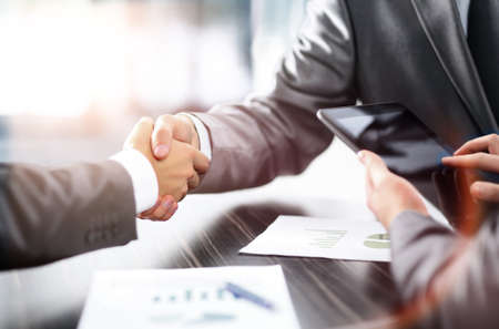 close: Business partners shaking hands at the table Stock Photo
