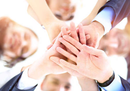team hands: Small group of business people joining hands, low angle view. Stock Photo