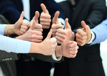 collaborator: Close-up of business team holding their thumbs up Stock Photo