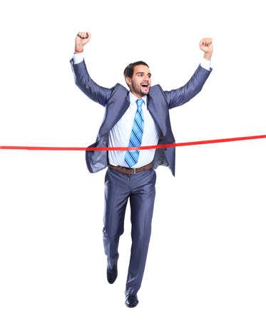 finishing line: Happy businessman running through finishing line. Isolated on white