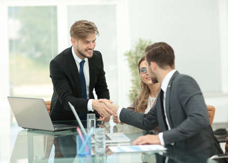 working hands: Happy smiling business man shaking hands after a deal in office