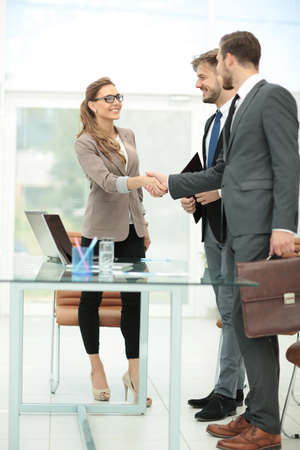 Happy smiling business people shaking hands after a deal in office Stock Photo
