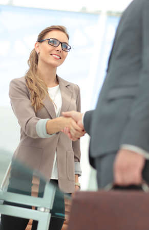 Happy smiling business people shaking hands after a deal in office Standard-Bild