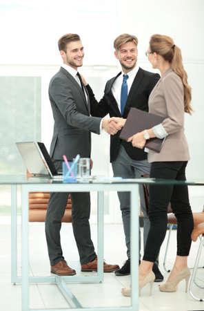 Succesvolle zakenpartners schudden handen met haar collega's op de achtergrond Stockfoto