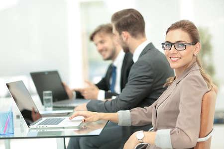 オフィスでラップトップに取り組んでいるビジネス人々 写真素材