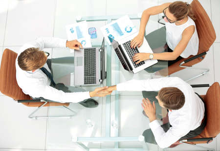 Image of business partners discussing ideas and working on laptops at meeting
