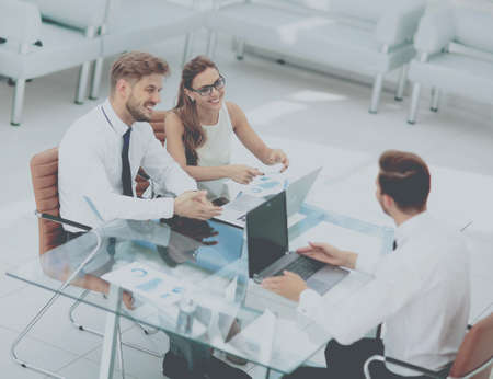 happy workers: Image of business partners discussing documents and ideas at meeting