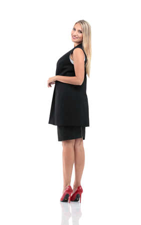 Full-length profile of businesswoman looking on camera, isolated on white. Stock Photo