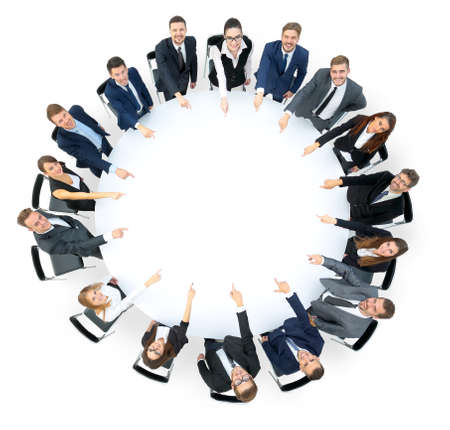 round: Diverse group pf young business people seated round a table discussing graphs in a business meeting. Pointing at something Stock Photo