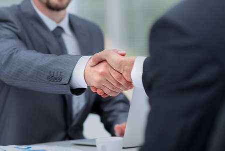 trust people: two smiling businessman shaking hands in office
