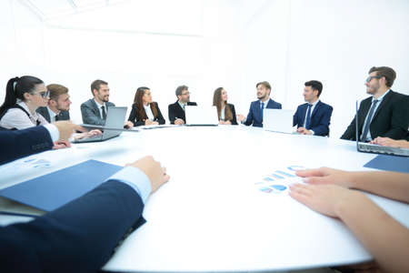 Business conference. Business meeting. Business people in formalwear discussing something while sitting together at the round table
