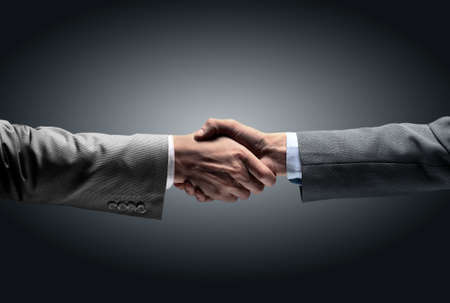 hand stretched out towards each other and shaking hands on a dark background. in the photo there is a blank for your text Stock Photo