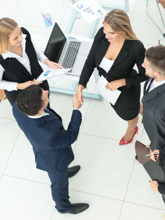 concluding: Diversity business team concluding contract with handshake in a modern office