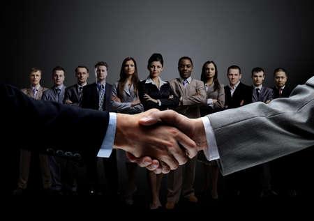apreton de mano: primer plano de apretón de manos de socios de negocios en el fondo de un equipo profesional de negocios en una foto background.The oscuro tiene un espacio vacío para el texto