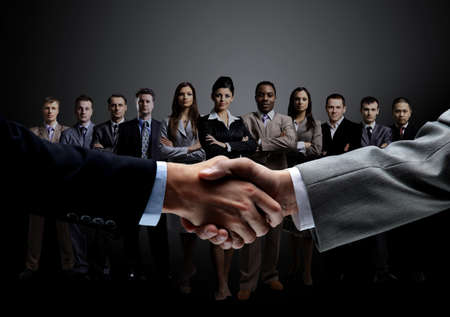 closeup of handshake of business partners on the background of a professional business team on a dark background.the photo has a empty space for your text Archivio Fotografico