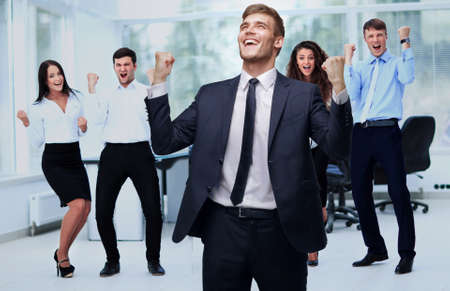 office man: closeup of happy businessman and cheering business team on office background Stock Photo