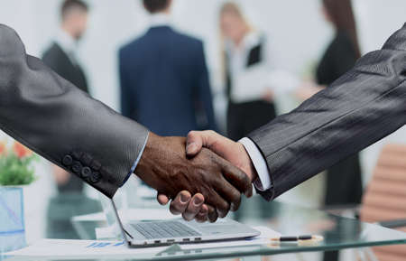 consent: closeup of handshake of business partners on the background of the financial documents in the workplace. photo has a empty space for your text