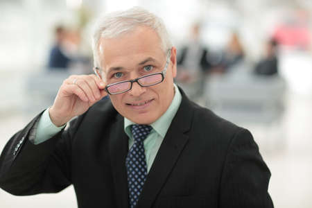 Mature friendly white-haired businessman in a modern office