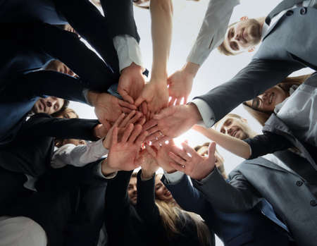 business relationship: Large business team showing unity with their hands together