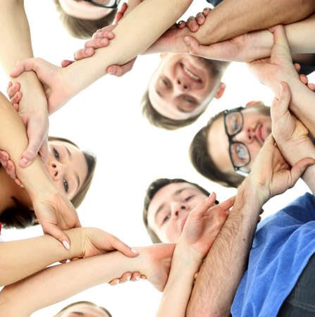 unity: friendship, youth and people concept - group of smiling teenagers with hands on top of each other