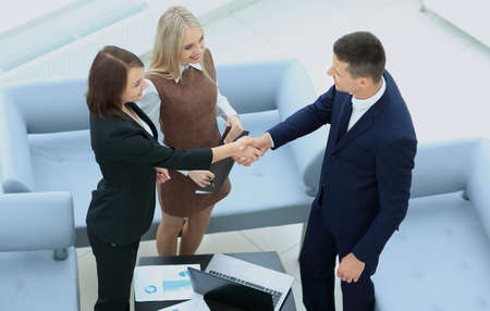 woman in office: An attractive woman and man business team shaking hands at office