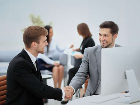 congratulating: Happy smiling business man shaking hands after a deal in office