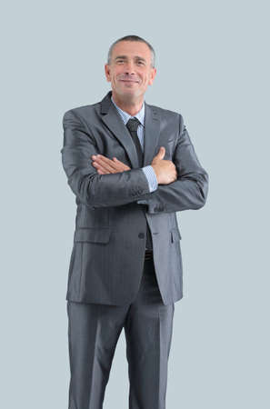 closeup of a successful and benevolent businessman in a business suit hands folded before him on the grey background.