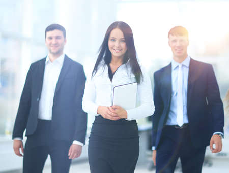 going in: Happy businessman going in front of her team Stock Photo