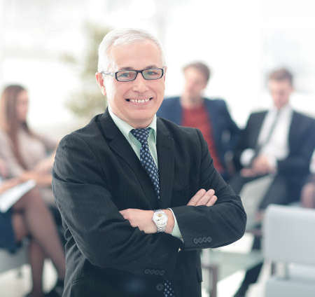 office man: Successful business man standing with his staff in background at office Stock Photo