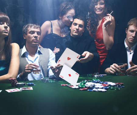 blackjack: Poker players sitting around a table at a casino Stock Photo