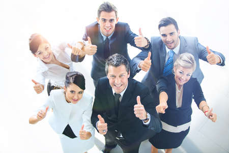 arms up: Top view of executives smiling and pointing