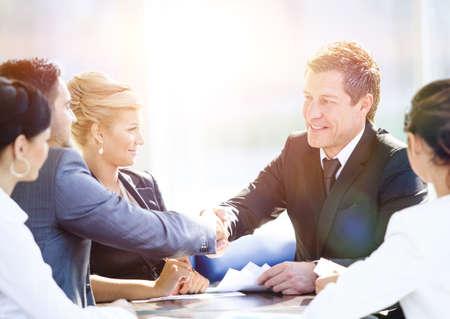 la union hace la fuerza: Colegas de negocios sentado en una mesa durante una reunión con dos ejecutivos hombres dándose la mano Foto de archivo