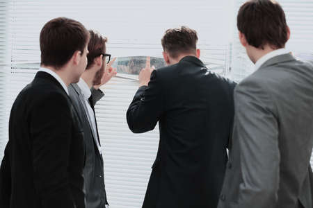 Business team looking through the office window, view from the back