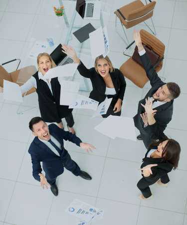Successful business team throws into the air the documents.