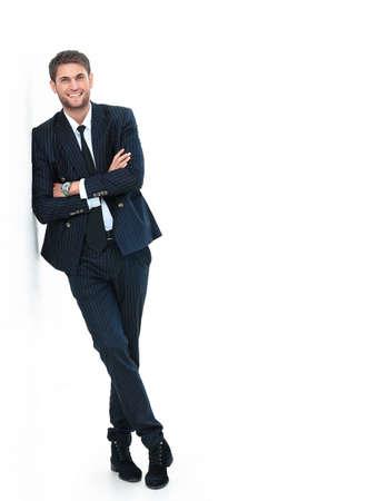 Retrato de un hombre joven y guapo con un traje de negocios. de pie cerca de la pared Foto de archivo