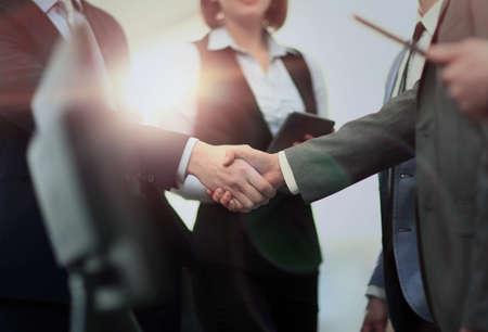 近代的なオフィスでビジネスの握手