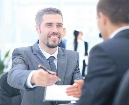 Businessman giving a pen his customer Stock Photo