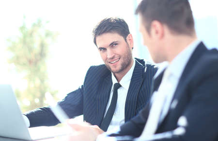 teamworking: Two businessmen discussing tasks sitting at office table.