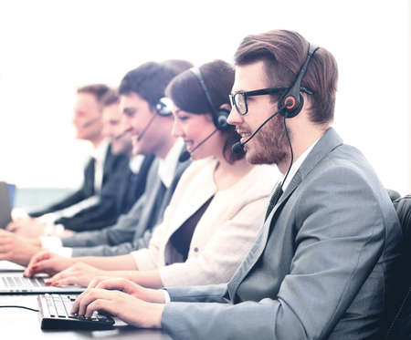Attractive young man working in a call center with his colleagues Stock Photo
